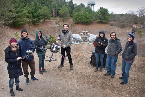 group of people standing with drone in front of radio telescope