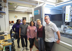 people standing in front of water jet cutter