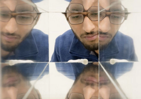 person looking in mirrors with several faces reflected