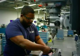 person working on a milling machine