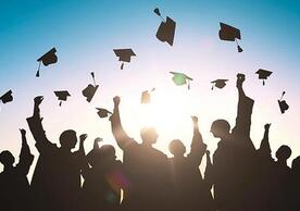 shadows of graduates throwing caps.